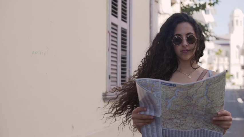 Young hipster woman traveler with map walking in old mediterranean city while doing sightseeing | Shutterstock HD Video #1029485786