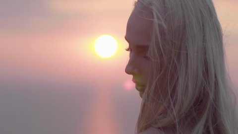Attractive blond woman at sunset, on top of a mountain, looking at camera in the late afternoon. Beauty shot golden hour 4K in slow motion.