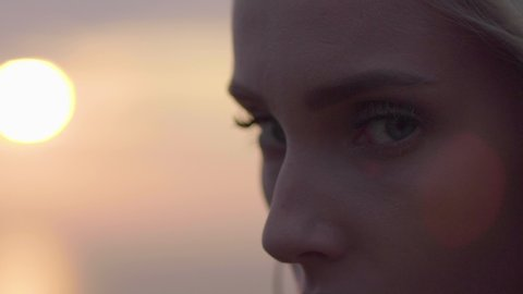 Attractive blond woman at sunset in extreme close up, on top of a mountain, looking at camera in the late afternoon. Beauty shot golden hour 4K in slow motion.