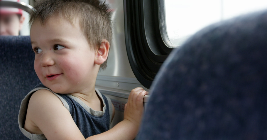 Toddler boy looks out window while riding public transportation - city bus | Shutterstock HD Video #1029565586