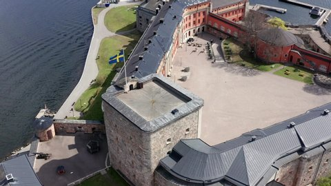 Vaxholm Fortress and Swedish flag in aerial drone shot. Military Island of Vaxholmen in the Stockholm archipelago
