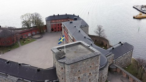 Beautiful aerial view of Swedish flag on Vaxholm Fortress. Circling drone shot around pole on top of military fort. Historic fortification on the island of Vaxholmen in the Stockholm archipelago