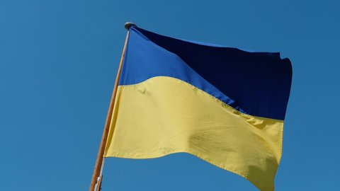 Big blue and yellow Ukrainian flag on the clear sky background. Symbol of Ukraine