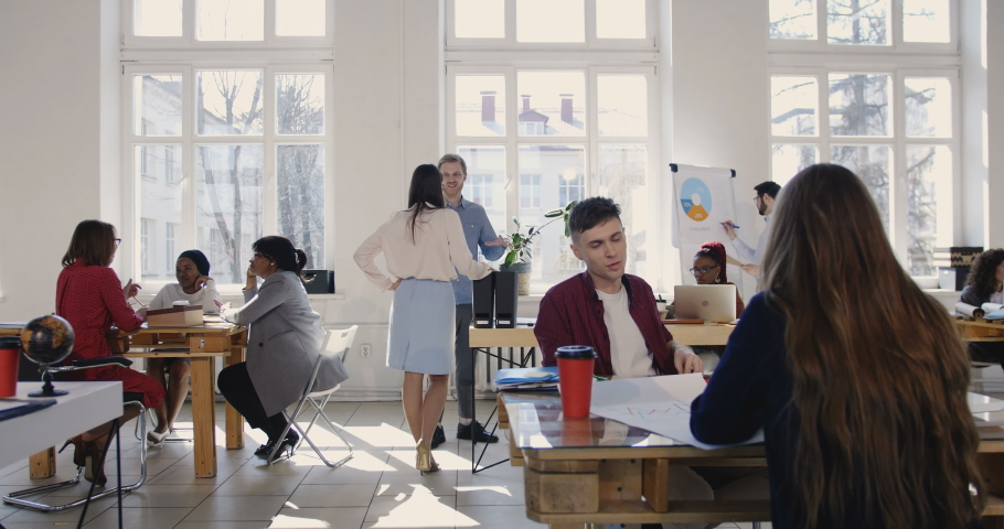 Camera slides left along trendy loft office, happy multiethnic business partners working at modern workplace atmosphere. | Shutterstock HD Video #1029657116