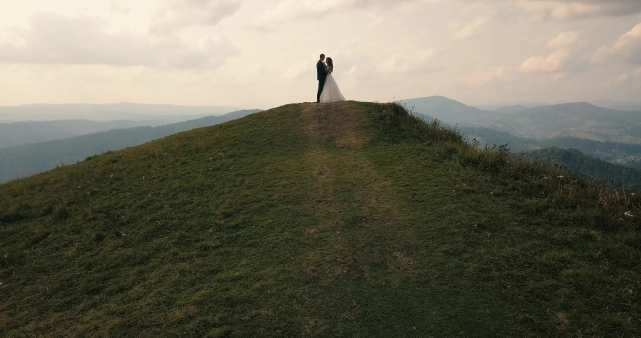 Bride and groom on the mountain in the Carpathians, aerial video #1029660356