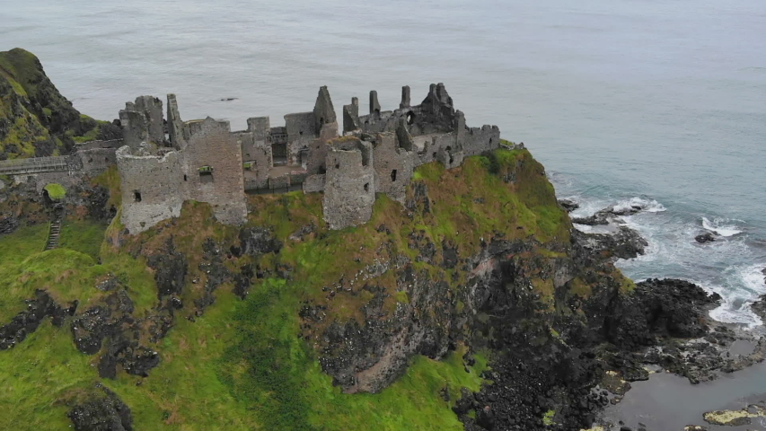 Tilted aerial shot, flying sideways over the Dunluce Castle ruins in Northern Ireland | Shutterstock HD Video #1029674756