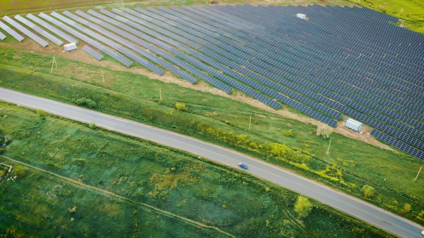 Aerial view of powerful station with solar panels generates electric current with help of sunlight is located in field near road on which pass cars. Drone shoots video of energy saving | Shutterstock HD Video #1029718106