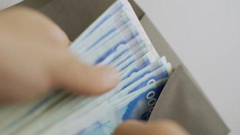 Hand puts large amount of Israeli money bills inside black envelope