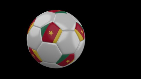Soccer ball with flag Cameroon flies past camera, slow motion blur, 4k footage with alpha channel