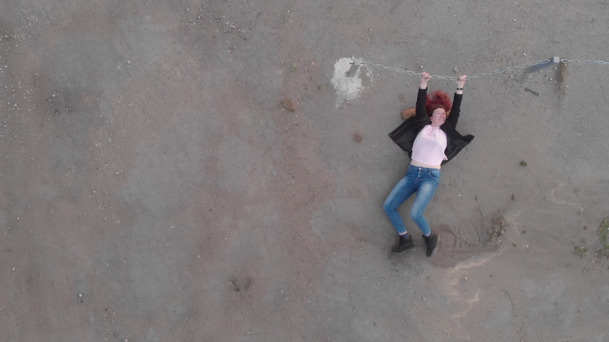 Aerial of Chained trapped woman concept acting like actress showing flag wearing blue jeans and pink t-shirt with a jacket - Caucasian white redhead girl - Top view from above | Shutterstock HD Video #1029857396