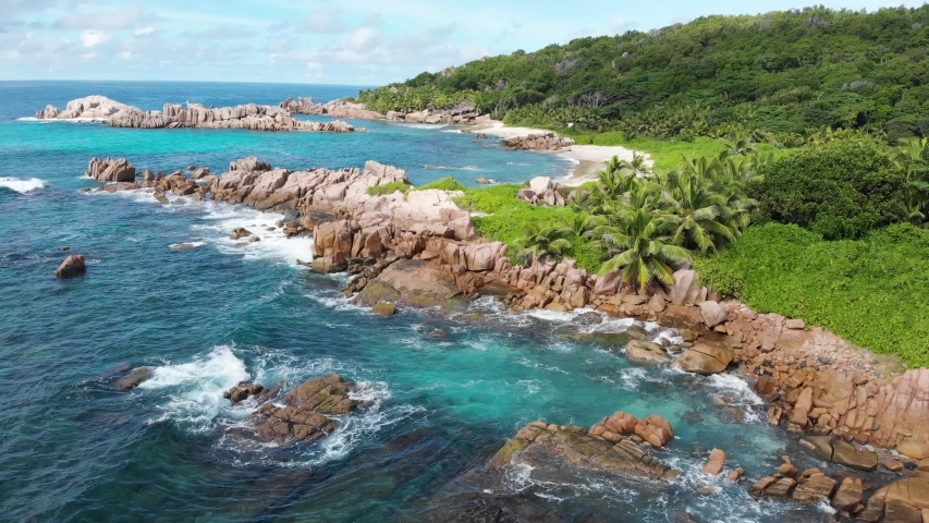 Aerial view of waves breaking at the unpeopled coastline at Anse Songe on La Digue, an island of the Seychelles. | Shutterstock HD Video #1029900056