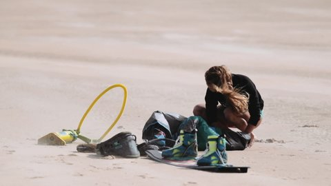 Dakhla, Morocco. April, 2018. Kitesurfing equipment strewn on beach sands and blond woman. Slow motion.