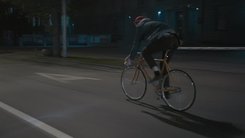 Unrecognizable male cyclist at night city street. Eco-friendly urban transport. Riding a bike with great speed. Active urban lifestyle concept. | Shutterstock HD Video #1029916136