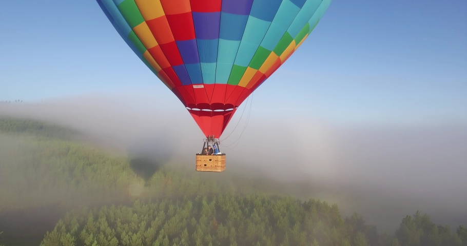 Colorful hot air balloon epic flying above mountain over the fog at sunrise with beautiful sky background - Aerial drone view | Shutterstock HD Video #1029942356