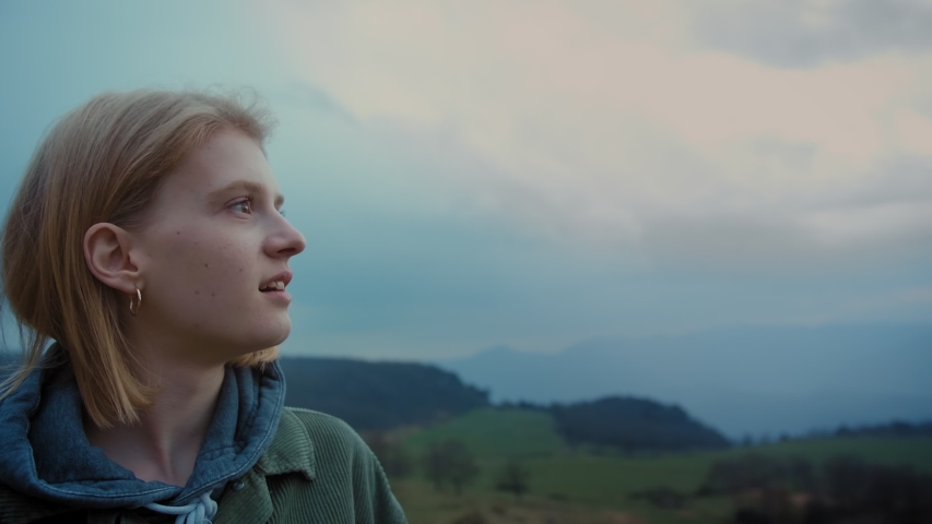 Caucasian cute bewildered female fascinated observing wild charming mountains at Spain, side portrait of looking into distance young hipster and enjoying breathtaking evening moment of freedom | Shutterstock HD Video #1029993326