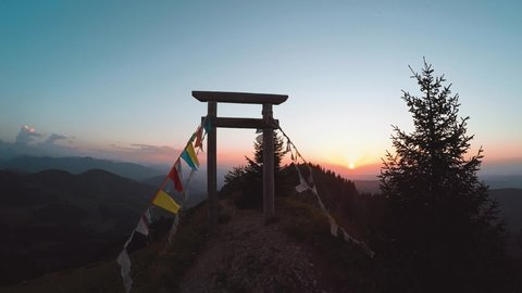 Slow motion, forward shot through a wooden gateaway with some fabric festoons attached, with a written texture,ing in the wind, on top of a mountain ridge, with mountains in the back, at sunset