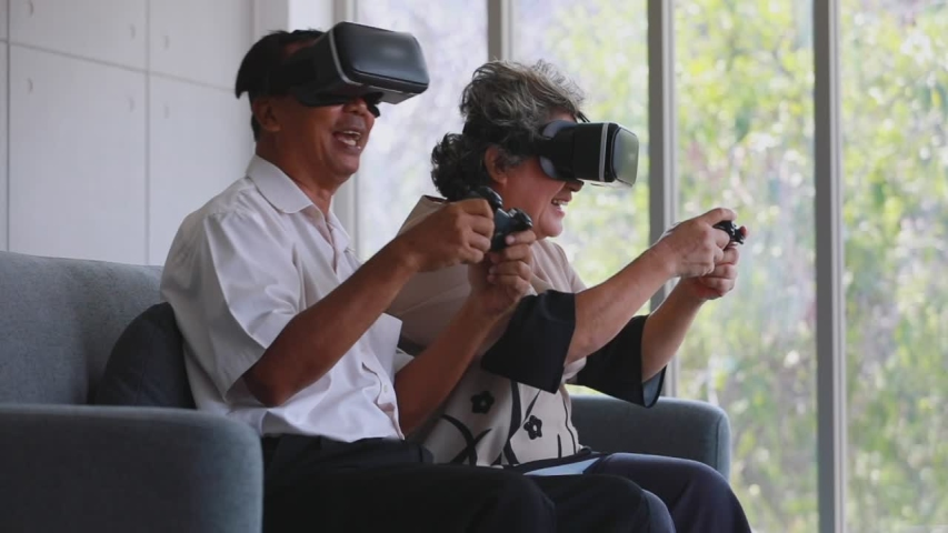 Slow motion scene video of senior Asian couple using VR device which are fun virtual computer or video games.  | Shutterstock HD Video #1030020266