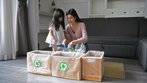 Family concept. Mom is teaching her daughter how to separate solid waste.