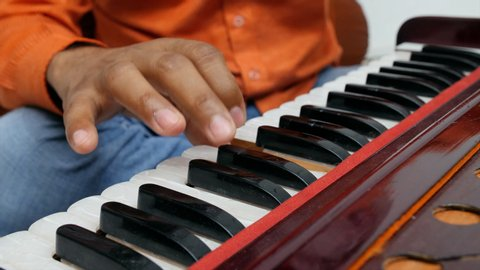 Close up shot of a musician playing Indian traditional musical instrument harmonium.