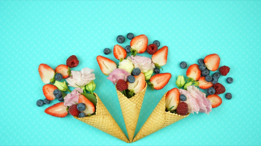 Summertime concept flatlay stop motion concept with ice cream cones filled with fruit, flowers and candy. | Shutterstock HD Video #1030097216