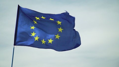 Slow motion EU European Union flag, Blue with gold circle of stars floating &ing slow motion in the wind against off white cloudy sky.