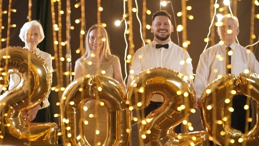 Medium shot of happy young and elderly men and women smiling and holding festive 2020 balloons in room with fairy lights   Shutterstock HD Video #1030112516
