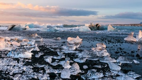 Time lapse of sea  waves with ice and small iceberg moving in sea - sunrise on ocean 4K. Dynamyc movement clouds atmosphere of travel to winter Iceland morning sea beach tourism black sand destination