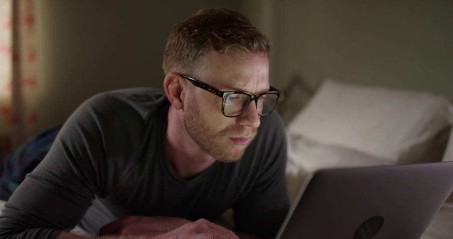4K Man in bedroom doing internet search late at night, could be student or businessman working from hotel room | Shutterstock HD Video #1030136126