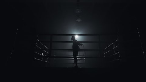 Male boxer wrapped in bandage jumping on the skipping rope in the dark ring. Slow motion. Silhouette. Boxing concept.