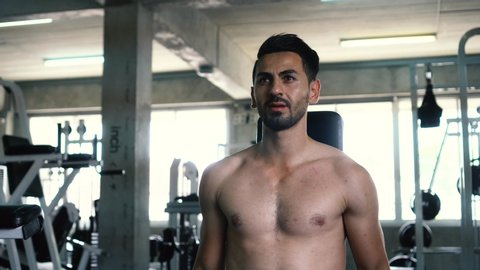 Muscular powerful young man doing biceps lifting with dumbbells in fitness gym. Caucasian male fit model working out indoors