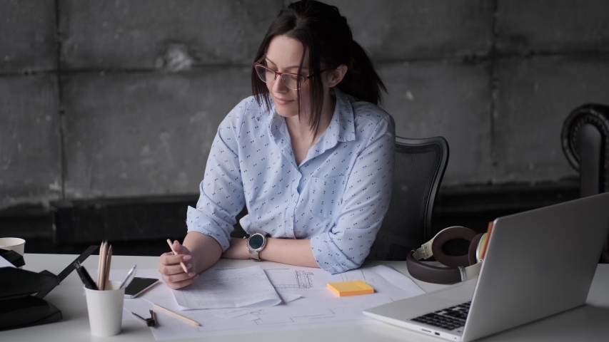 Young female architect working with plans and documents while sitting at the table in the office. | Shutterstock HD Video #1030199906