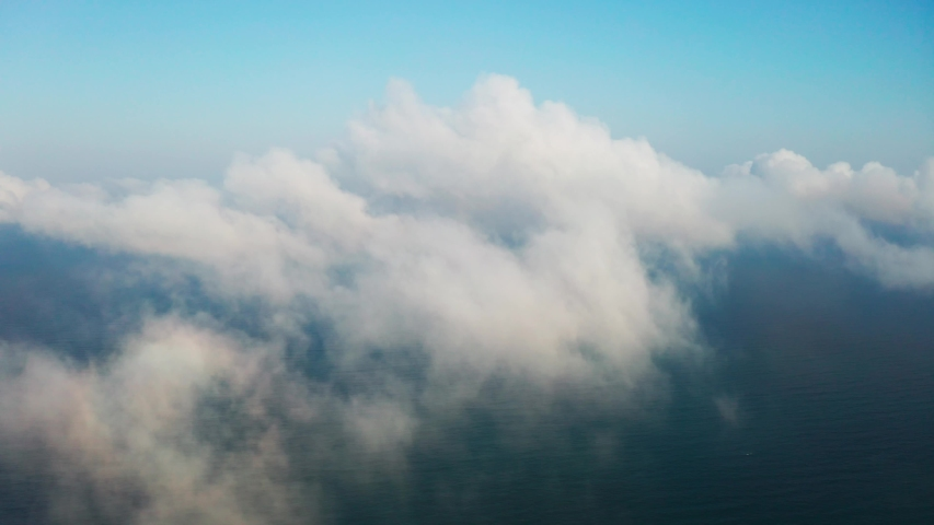 Scenic aerial view through moving white clouds onto sea surface. The drone slide flies forward high in the blue sky through the fluffy clouds on the panorama the sea shore. The sun is hidden behind  | Shutterstock HD Video #1030212056