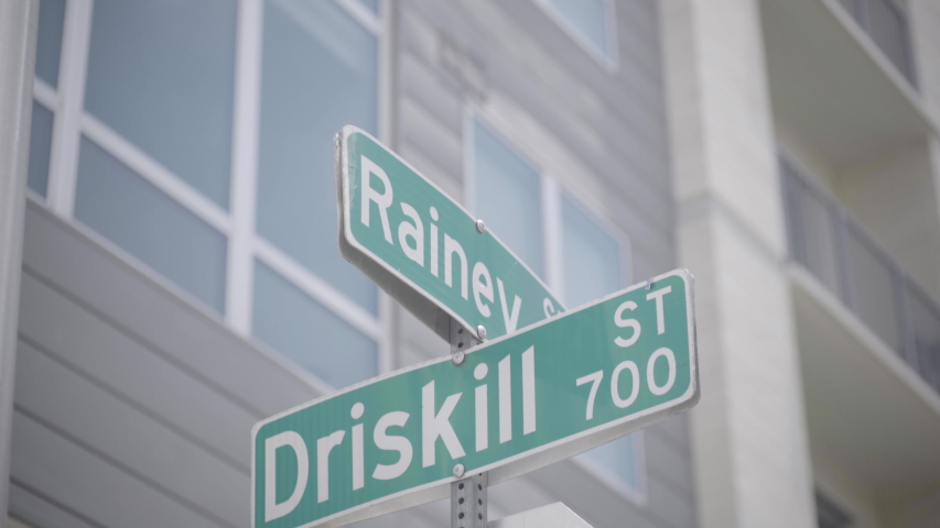 The street signs for Rainey street and Driskill street in Austin, Texas - slight camera movement | Shutterstock HD Video #1030223516