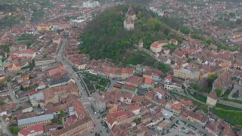 Drone Aerial Tilt Down Footage of Sighisoara Town in Transylvania Romania With Hills Parks Buildings in City Center and Traffic