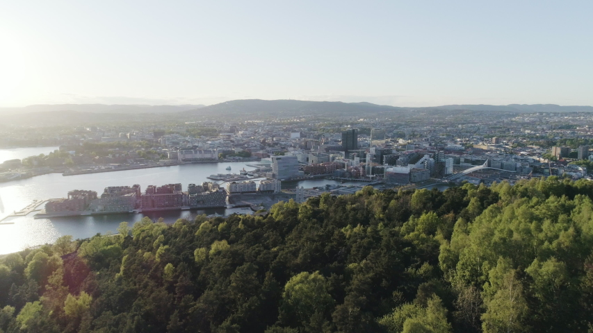 4K aerial of the Oslo city line with a backdrop of downtown Oslo and the construction of Bjoervika, a popular tourist attraction with the Munch museum, Barcode and Soerenga pier, with forward motion. | Shutterstock HD Video #1030387676