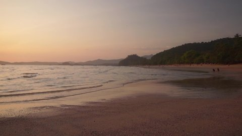 Beautiful beach Ao Nang in the province of Krabi at sunset. The warm waves of the Andaman Sea gently wash the sand of the beach in the evening. 50 frames per second full hd footage.