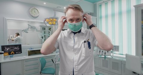 male adult middle aged doctor protects himself with surgical mask. european serious dentist prepare to take client in medical office follows sanitary rules.