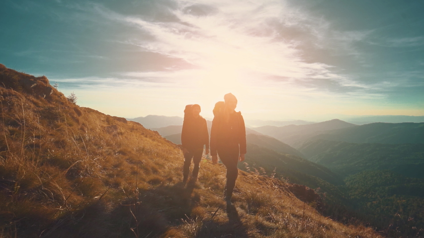 The couple walking in mountains against the sunset background. slow motion | Shutterstock HD Video #1030416056