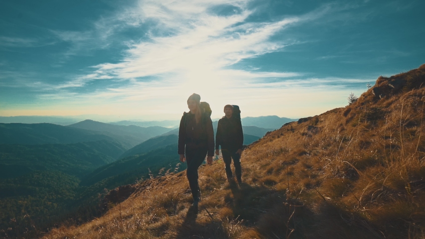 The couple walking along the evening mountain. slow motion | Shutterstock HD Video #1030416116