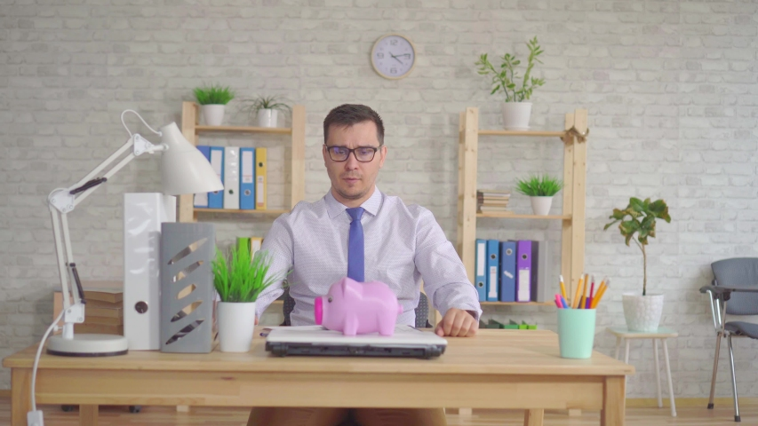 Young man in a shirt and glasses sitting in the office puzzled looks at the piggy Bank | Shutterstock HD Video #1030427336