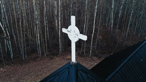 Aerial orbital of white cross on mysterious church and gloomy woodland while snowing