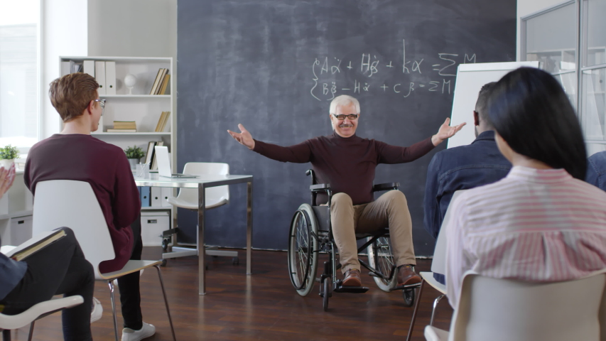 Cheerful mature professor sitting in wheelchair entering classroom and smiling, multiethnic students clapping hands and greeting him | Shutterstock HD Video #1030463576