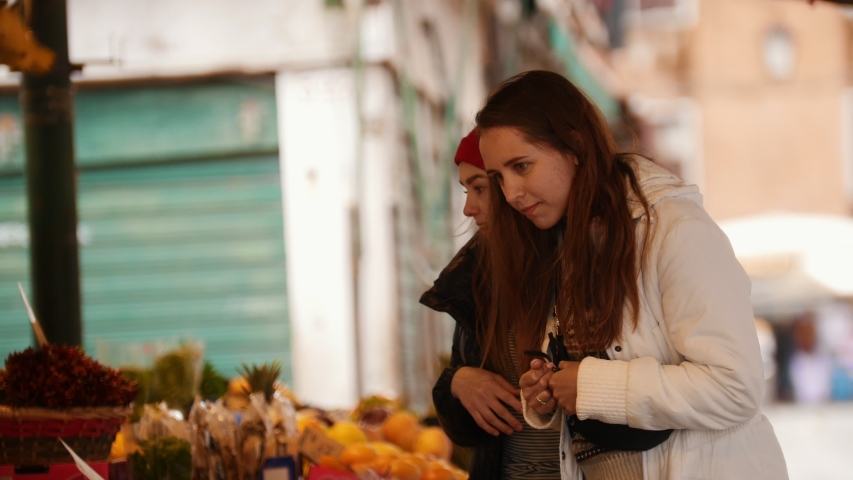 Two young women walking on the outside market and looking for exotic sweets | Shutterstock HD Video #1030511066