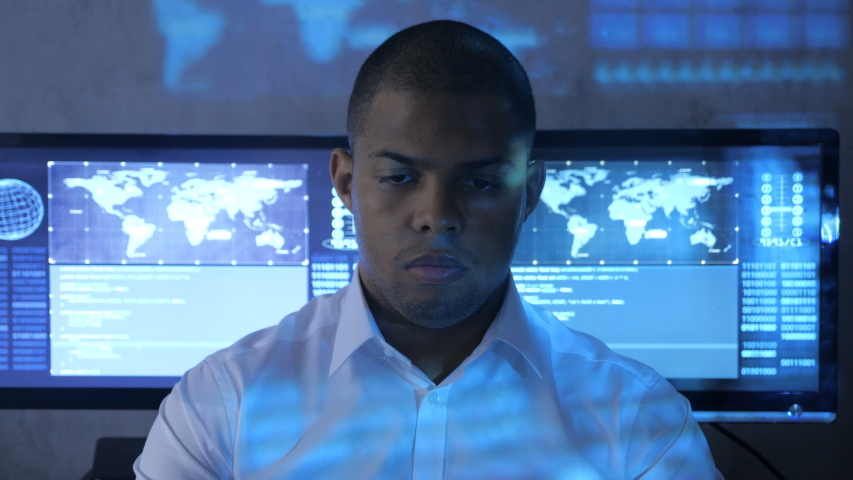 Portrait of African American man programmer in white shirt working on computer in security data center. Holographic code on his face | Shutterstock HD Video #1030563176