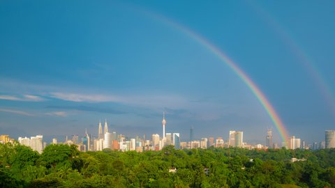 Time lapse: Kuala Lumpur city day view after rain with clear rainbow overlooking the city skyline from afar with lushes green trees. Federal Territory, Malaysia. Pan down motion timelapse.