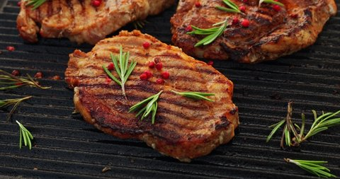 Grilling pork steaks, pork neck with the addition of herbs and spices on the grill plate, top view, 4k. Grilled meat, bbq, barbecue