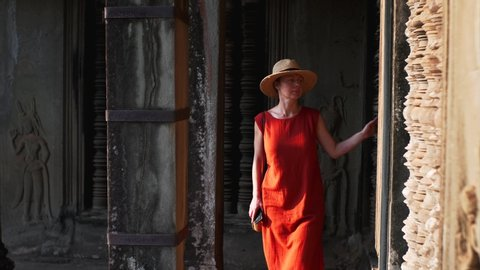 Woman in red dress is exploring corridors and amazing carvingsg of ancient Angkor Wat temple, built in 12th century in Cambodia and dedicated to Vishnu. Cambodia