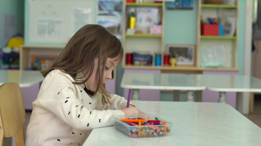 Side view. Child alone in kindergarten. Charming girl alone in kindergarten waiting for parents, dad and mom. She draws. | Shutterstock HD Video #1030679726