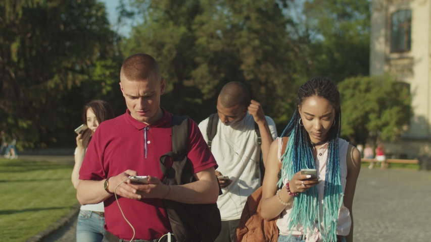 Group of multinational college students obsessed with smartphones walking, ignoring everything around them on university campus. Multi ethnic young people phubbing each other using mobile app outdoors | Shutterstock HD Video #1030736186