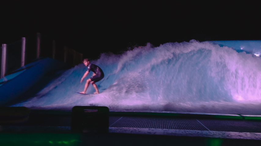 Boy with Wetsuit Surfing on a standing artificial wave during night falling. Blue water with light operated with engines. #1030739546